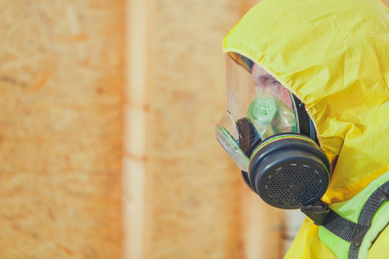 A worker in protective gear working on asbestos removal inside a home.